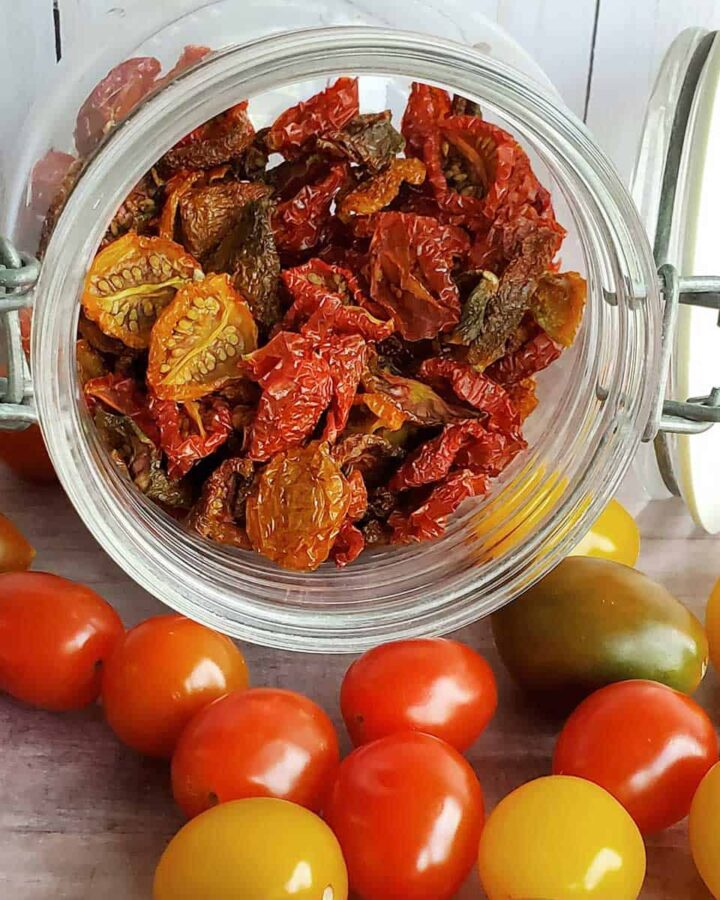 Jar of dehydrated cherry tomatoes spilling out to fresh cherry and grape tomatoes on table top