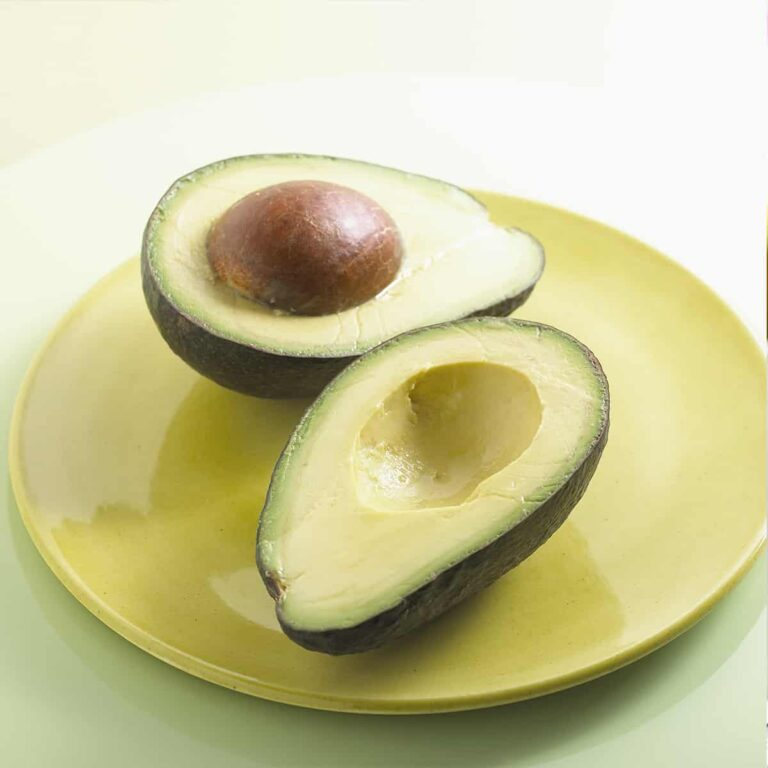 Halved avocado with seed on a yellow plate