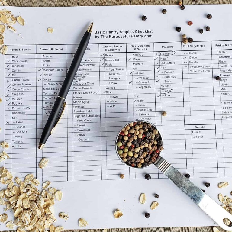 Pantry list on a table with scattered pantry staples, a pen, and a measuring spoon of peppercorns