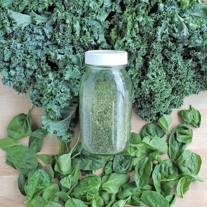 Jar of dehydrated green powder laying on a bed of kale and spinach