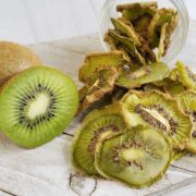 Fresh sliced kiwi with dehydrated kiwi slices falling out of a mason jar onto a white wooden surface
