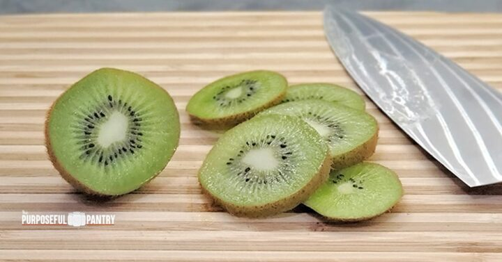 Sliced fresh kiwi on a wooden cutting board with a chef's knife