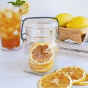 Dried lemon slices in a jar, on the table, and one in a glass of iced tea.