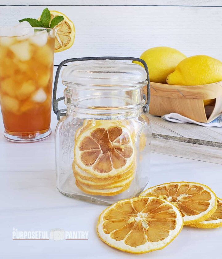 Dried lemon slices in a jar, on the table, and one in a glass of iced tea. and fresh lemons