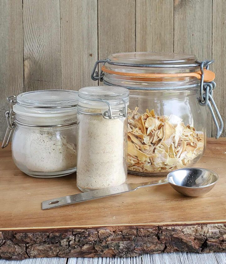 Dehydrated Onions in a clamp glass jar with onion powder in a measuring spoon