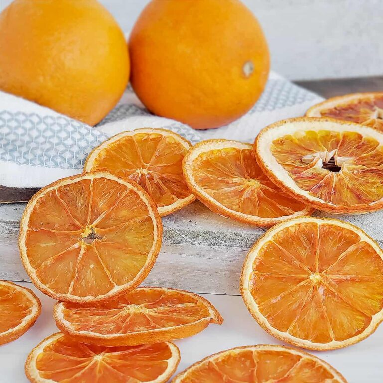 Fresh oranges with sliced dried oranges across the surface