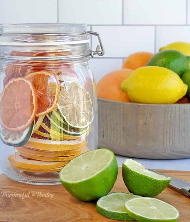 Jar of dehydrated citrus rounds in front of a bowl of fresh citrus, along with cut limes on a cutting board.