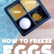 Eggs broken into ice cube compartments for freezing - in different quantities. On a blue cloth and wooden surface
