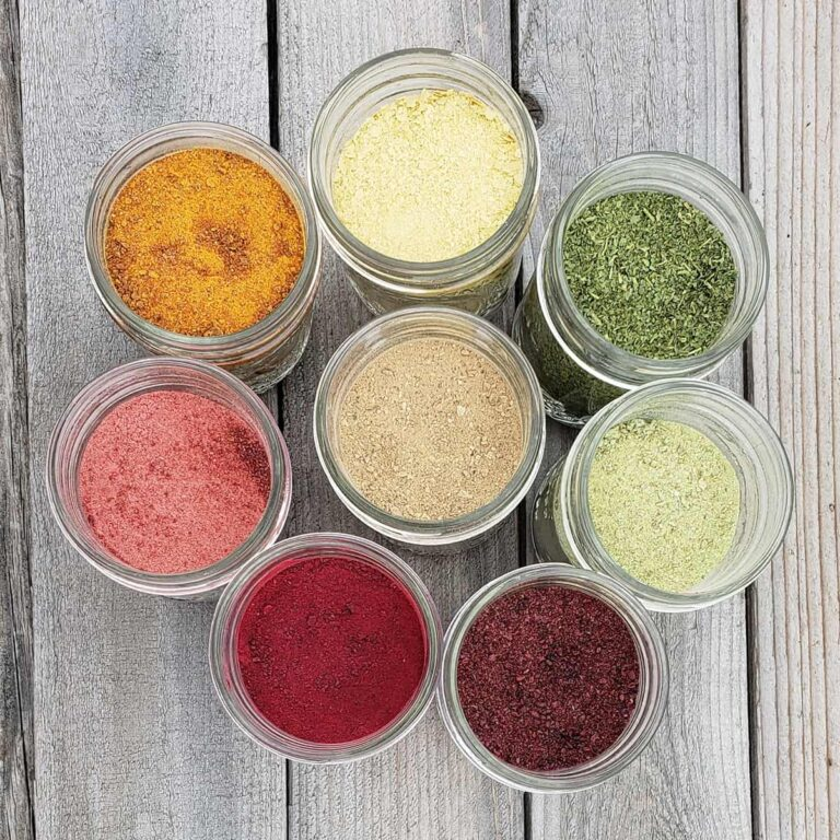 Various vegetable and fruit powders in the colors of the rainbow in circle on a wooden surface