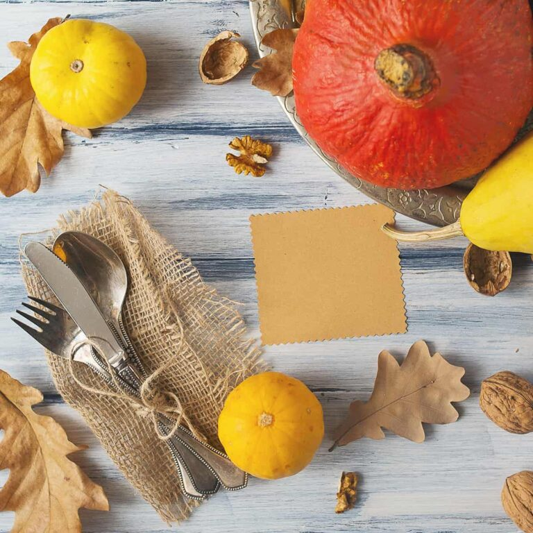 Thanksgiving tablescape from above - utensils, napkin, pumpkins a nd nuts on a wooden surface