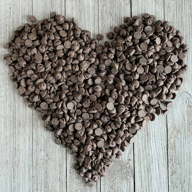 Chocolate chips in pile that have been formed into a heart-shape on a wooden surface