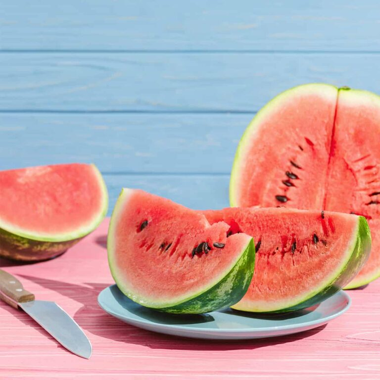 Watermelon sliced, halfed, and served on blue dinnerware