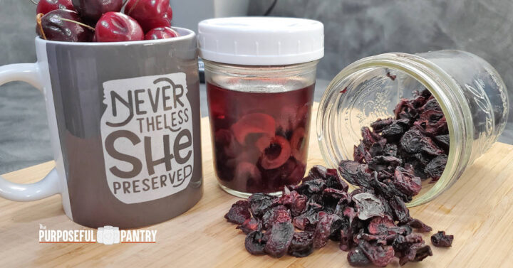 Cherries in a coffee mug, next to rehydrating cherries, and dried cherries spilling out of a canning jar