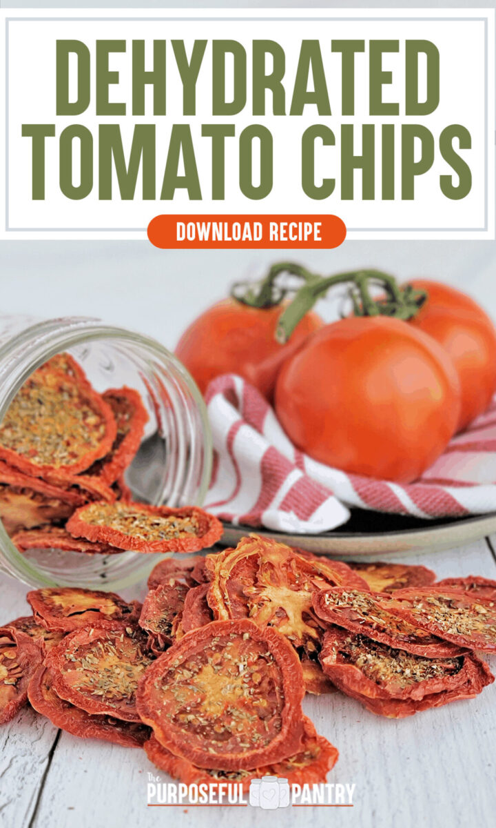 Dehydrated tomato chips on a wooden table with fresh tomatoes in the background