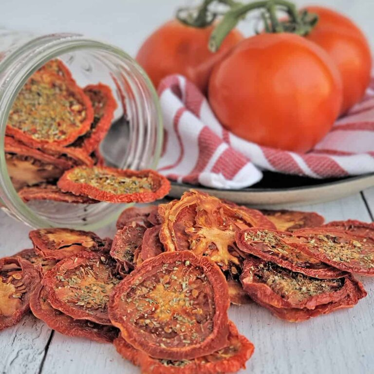 Seasoned dried tomato chips spilling from a mason jar, fresh vine ripe tomatoes on red striped towel in background.