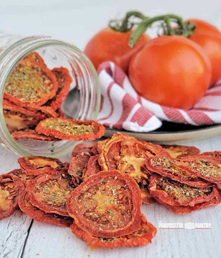 Dried tomato chips spilling onto a table from a jar, fresh tomatoes in the background