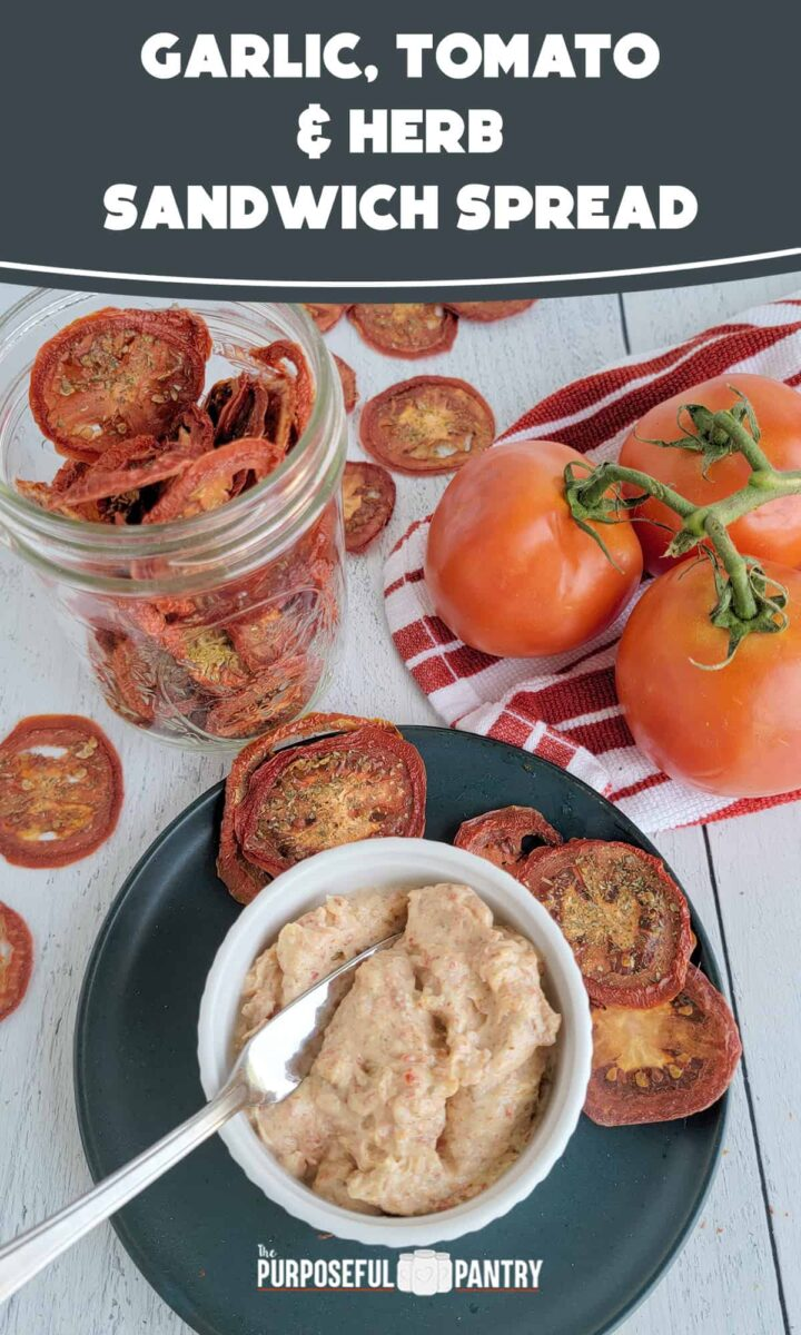 Pin Image fo garlic tomato spread on a blue plate with dried tomato slices and fresh tomatoes on a wooden surface