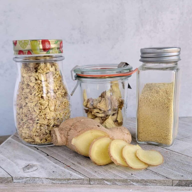 Jars of dried minced gigner, ginger slices, and ginger powder with fresh ginger laying on a white cutting board.