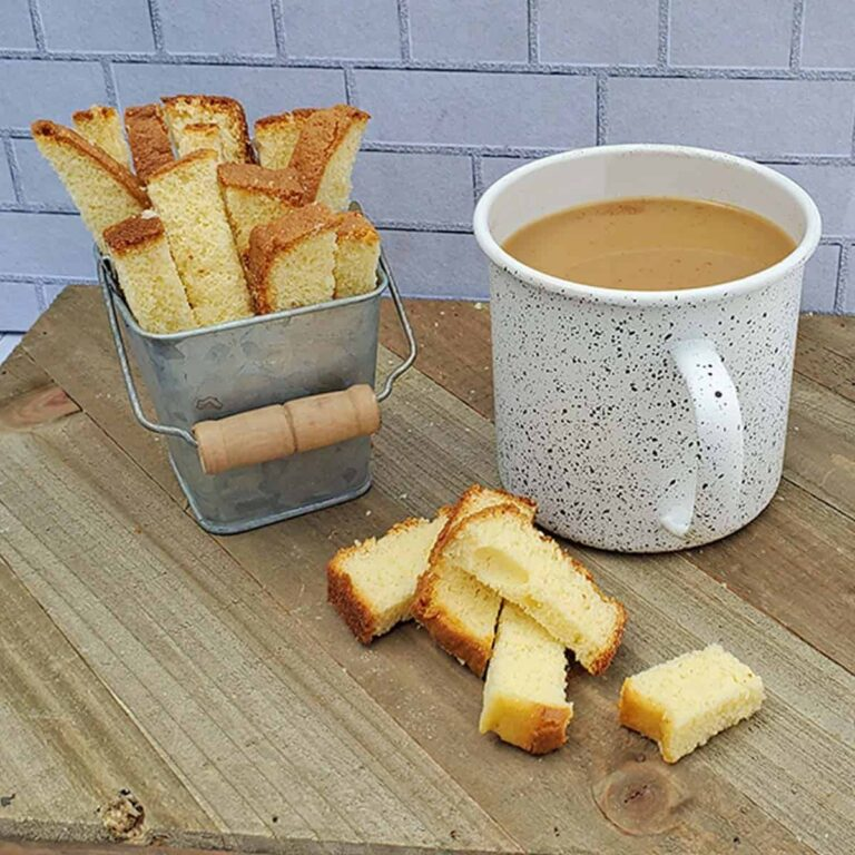 pound cake biscotti on a wooden surface with a cup of coffee in white speckled mug