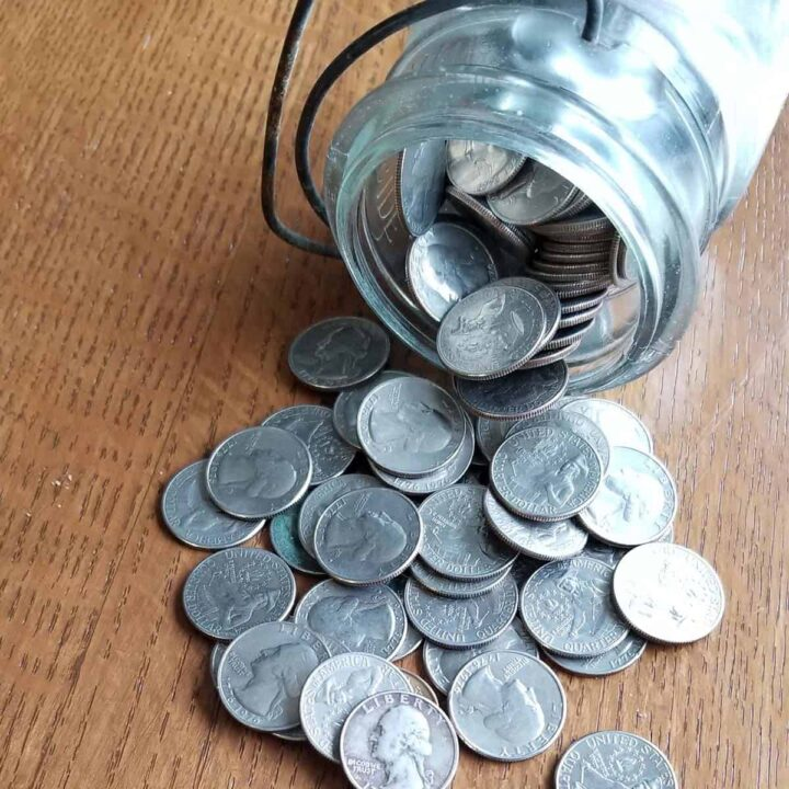 Jar of quarters spilled out onto a table signifying an emergency fund