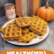 Stack of pumpkin waffles with canned pumpkin puree and some pumpkin decor in the background