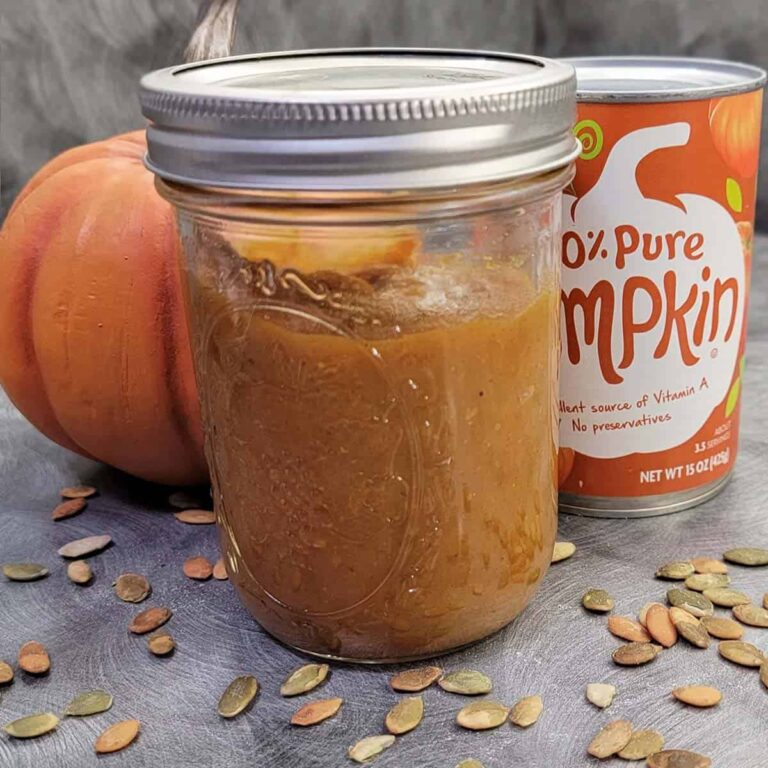 A canning jar of homemade pumpkin butter, with a can of pumpkin puree and pumpkin decor in the background, foreground sprinkled with pepitas